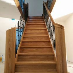 ST104. Two Oak staircases with wrought iron and curved newel posts (taken mid-installation)