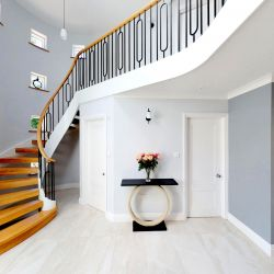 ST105. Curved Oak and white Birch staircase with custom-made Artistic Wrought Iron