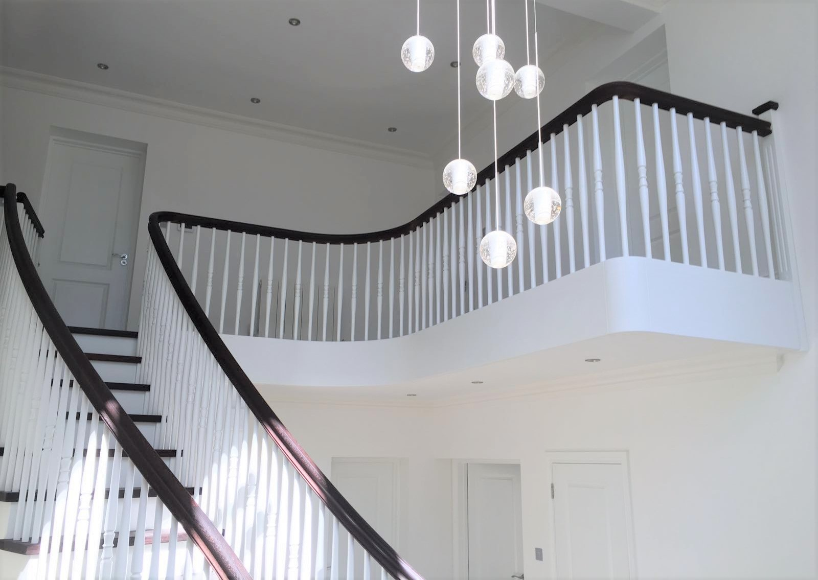 White curved stairs with black handrails by WoodenStairs