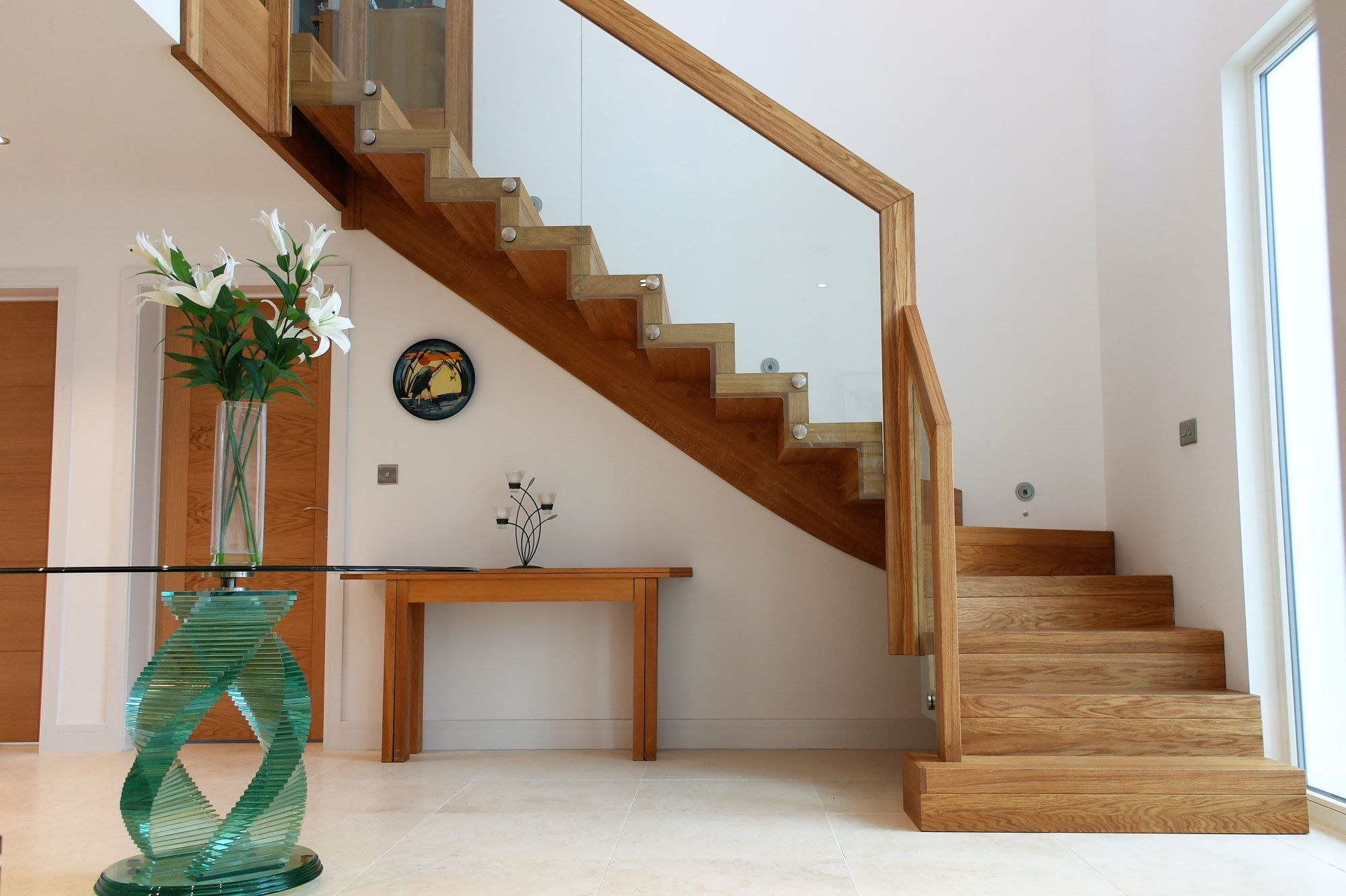An Oak wooden staircase with glass by WoodenStairs with flowers