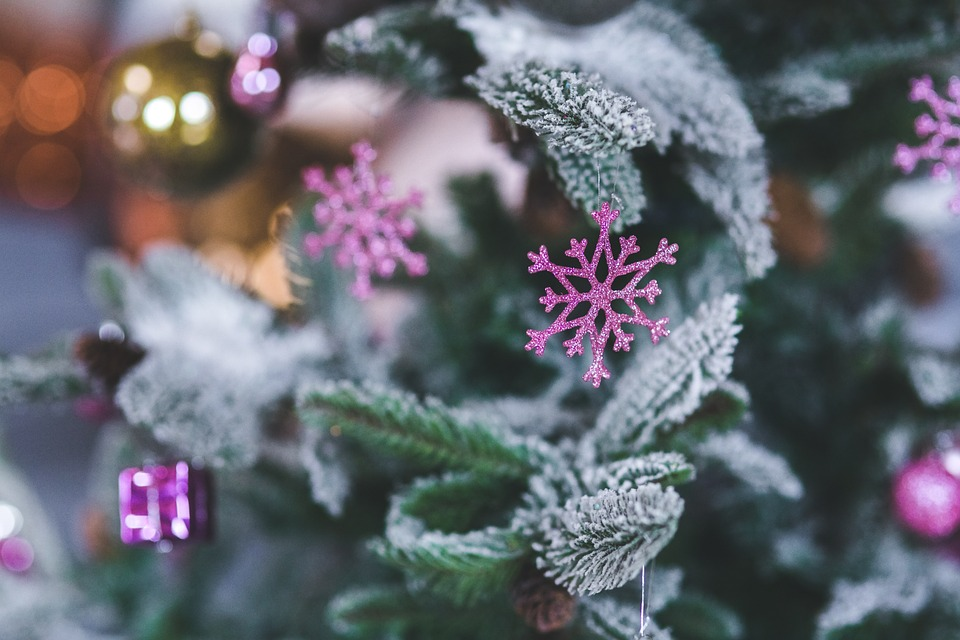 Pink snowflake decorations on a snow-covered Christmas tree