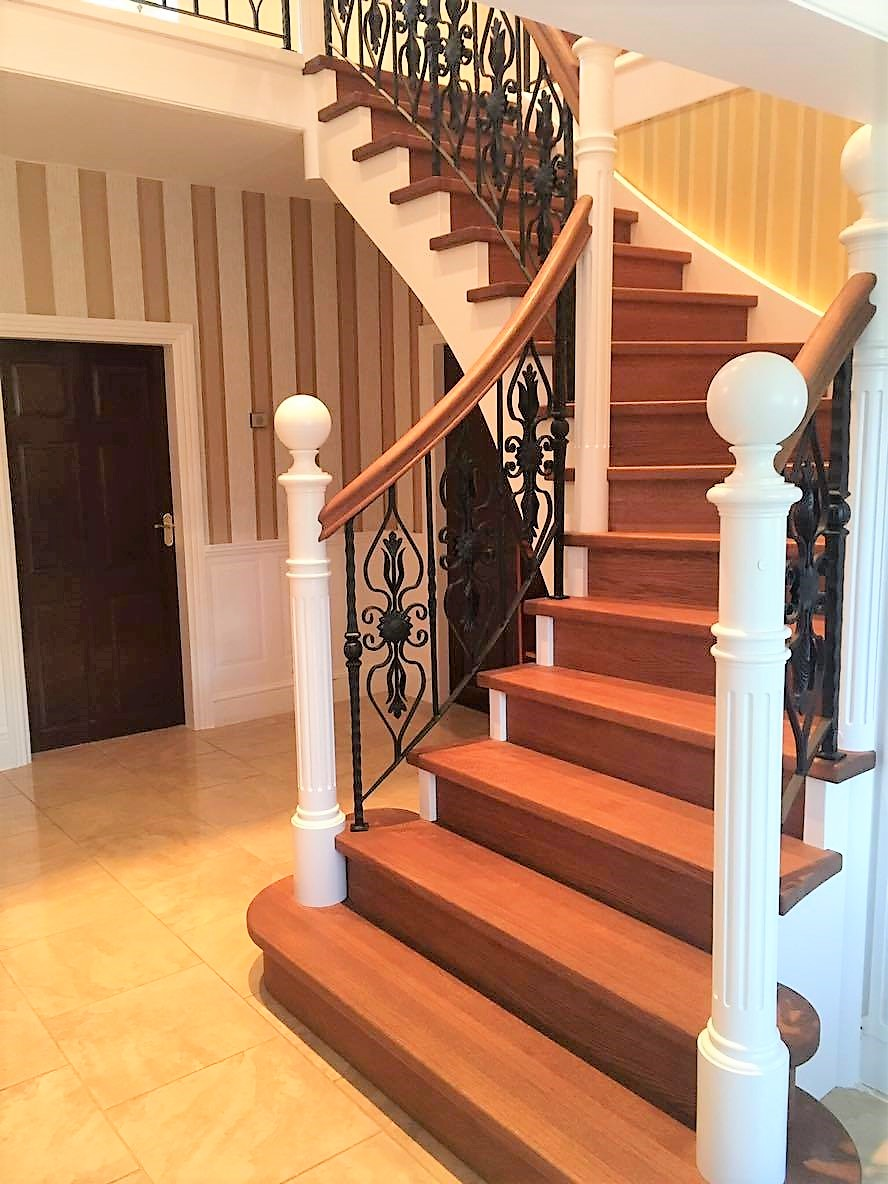 Metal and wood stair railing with hand-made wrought iron motifs