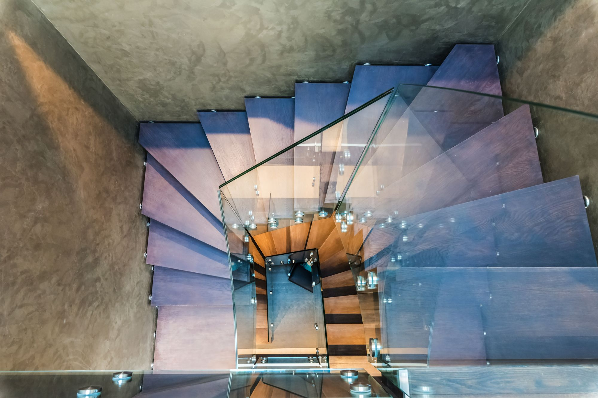 Grey wood zigzag stairs with glass
